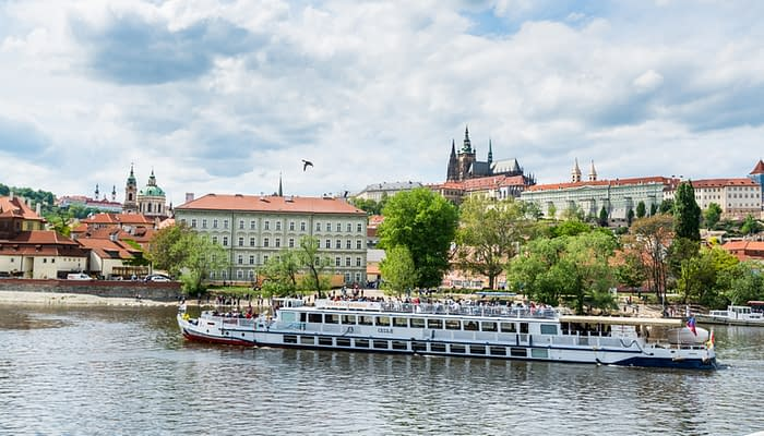 Cruise ship sailing on the Vltava River, with the background of Prague Castle, the world's largest one in the world.